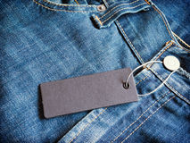 Label gray price tag mockup on blue jeans. Stock Images
