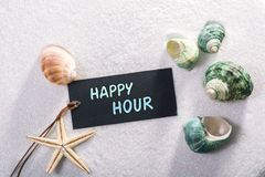 Label with happy hour. A natural looking label with happy hour written on it with sand and seashell and star royalty free stock photos
