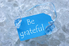Label On Ice With Be Grateful. Light Blue Label With Blue Ribbon On White Transparent Curshed Ice Cubes As Background. English Text Be Grateful For Cool royalty free stock images