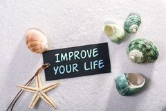 Label with improve your life. A natural looking label with improve your life written on it with sand and seashell and star Stock Photography
