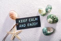 Label with keep calm and enjoy. A natural looking label with keep calm and enjoy written on it with sand and seashell and star Stock Image