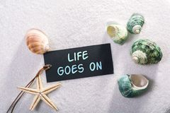 Label with life goes on. A natural looking label with life goes on written on it with sand and seashell and star Stock Photo