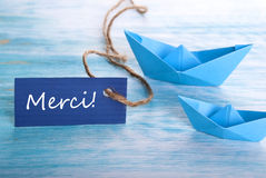Label with Merci and Boats. Label with the French Word Merci which means Thanks and two Boats in the Background Royalty Free Stock Image