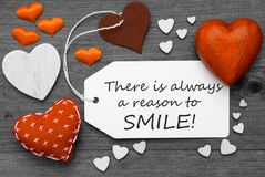 Label With Orange Hearts, Quote Always Reason To Smile. Label With Orange Textile Hearts On Wooden Gray Background. English Quote There Is Always A Reason To royalty free stock photography