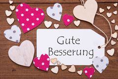 Label, Pink Hearts, Gute Besserung Means Get Well Soon. One Label With German Text Gute Besserung Means Get Well Soon. Flat Lay View With Wooden Vintage stock photos