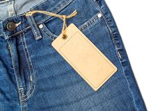 Label price tag mockup on blue jeans. Label price tag mockup on blue jeans from recycled paper Royalty Free Stock Photography