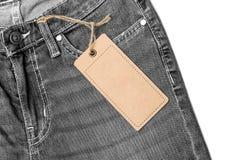 Label price tag mockup on blue jeans. Label price tag mockup on blue jeans from recycled paper Stock Photo