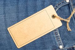 Label price tag mockup on blue jeans. Label price tag mockup on blue jeans from recycled paper Royalty Free Stock Images