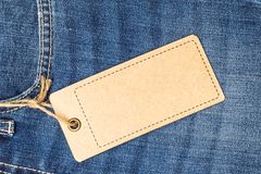 Label price tag mockup on blue jeans. Label price tag mockup on blue jeans from recycled paper Royalty Free Stock Photos