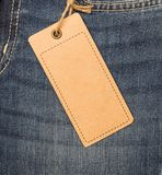 Label price tag mockup on blue jeans. Label price tag mockup on blue jeans from recycled paper Stock Photos