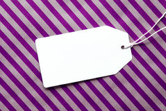 Label On Purple Wrapping Paper And Copy Space. One Label On A Purple Striped Wrapping Paper. Textured Background. Tag With Ribbon. Copy Space For Advertisement Stock Photography