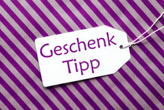 Label On Purple Wrapping Paper, Geschenk Tipp Means Gift Tip Stock Photography