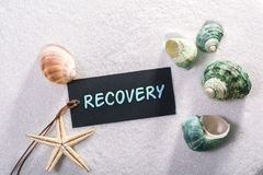 Label with recovery. A natural looking label with recovery written on it with sand and seashell and star royalty free stock photos