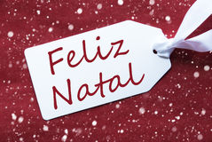 Label On Red Background, Snowflakes, Feliz Natal Means Merry Christmas. One White Label On A Red Textured Background. Tag With Ribbon And Snowflakes. Portuguese Stock Photography