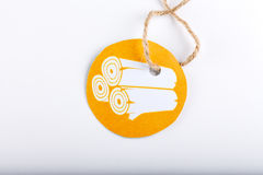 Label with rope. Orange paper labble with rolled fabric with a rustic rope attached stock image