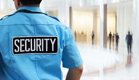 Security guard in the business office. Label `security` on guard uniform in the business office stock photos