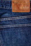 Label sewed on a blue jeans Stock Photos