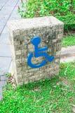 Label sign of cripple. Design on brick block on nature park Royalty Free Stock Photo