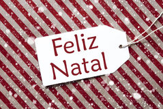 Label sur le papier rouge, Feliz Natal Means Merry Christmas, flocons de neige Photographie stock