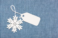 Label tag and snowflake on jeans. Blank paper label tag and snowflake on  blue jeans Stock Photography
