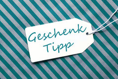 Label On Turquoise Wrapping Paper, Geschenk Tipp Means Gift Tip Stock Photography