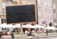 Label vide de tableau noir et un point de repère urbain brouillé Images stock