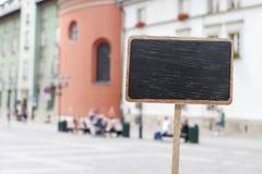 Label vide de tableau noir et un point de repère urbain brouillé Photographie stock libre de droits