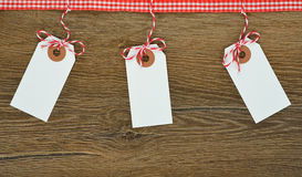 Labels on brown background. White labels decorated with a ribbon on a brown background royalty free stock photography