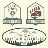 labels d'aventure de vintage avec l'ours, les saumons et les montagnes Photographie stock