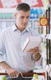 Labels de nourriture de lecture d'homme photo stock