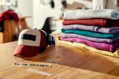 Labels that enhance your image. Custom apparel, clothes neatly folded on shelves. Stack of colorful clothing and