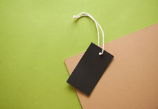 Labels on green background. Empty clothes` labels with vivid shadows on colorful background Stock Image