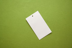 Labels on green background. Empty clothes` labels with vivid shadows on colorful background Royalty Free Stock Images