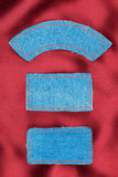 Labels made of jeans lying on the red silk Royalty Free Stock Image