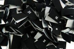 Labels noirs de taille d'habillement de tissu Photo stock