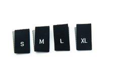 Labels noirs de taille d'habillement de tissu images stock