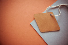 Labels on orange background. Empty clothes` labels with vivid shadows on colorful background Royalty Free Stock Photos