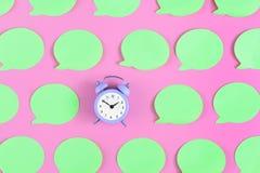 Labels vert clair lumineux et vides sur un fond rose Au centre est un petit réveil lilas Concept, beau Photos libres de droits