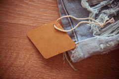 Labels on wooden background. Empty clothes` labels with vivid shadows on colorful background Stock Photography