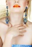 Labios anaranjados y earings azules Imágenes de archivo libres de regalías