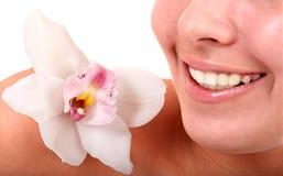 Labios de la muchacha y flor de la orquídea. Salón del balneario. Fotos de archivo