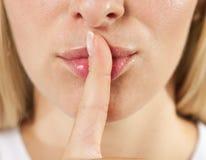 Labios de la mujer con el shh del dedo Fotos de archivo