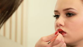 Labios de la pintura del artista de maquillaje del primer hermoso de la mujer joven almacen de video