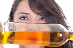 Labios de ocultación de la muchacha latina detrás de una botella amarilla Imagenes de archivo