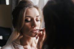 Labios de pintura del artista de maquillaje con la barra de labios desnuda en la cara c de la novia foto de archivo libre de regalías