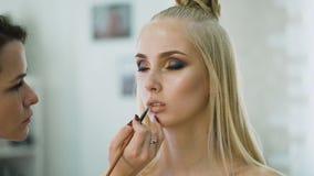 Labios delicados de una chica joven Maquillaje perfecto en el blonde radiante de la piel almacen de metraje de vídeo