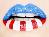 Labios femeninos hermosos pintados con el indicador americano Fotos de archivo