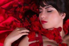 Labios rojos y pétalos color de rosa Imagen de archivo