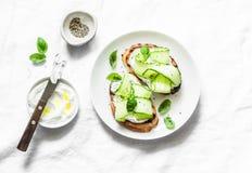 Labne和酱瓜在轻的背景,顶视图敬酒 三明治用软干酪和黄瓜-可口健康增殖比 免版税库存图片