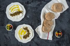 Labneh labaneh middle eastern soft white goat`s milk cheese with olive oil ,olives , za`atar , lemon, with pita bread over blac stock photo